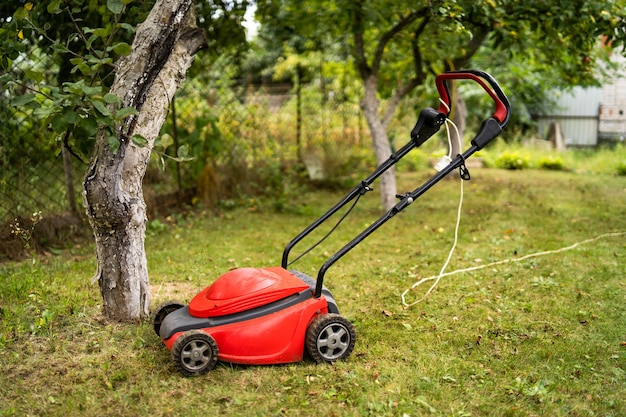 Red lawn mower outdoor in the backyard. green grass and fruit trees background