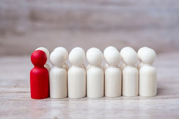 Red leader businessman with crowd of wooden men. leadership, business, team, teamwork and human resource management concept