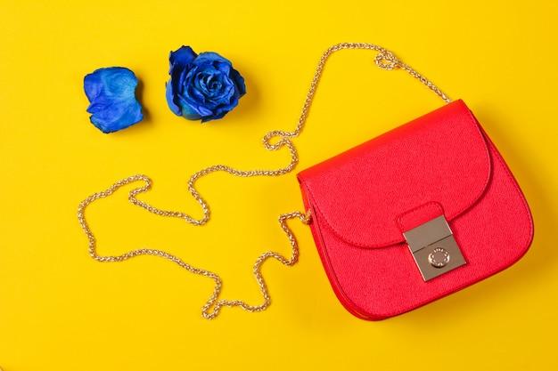 赤い革のバッグと青いドライローズの芽。上面図