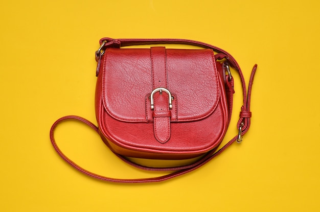Red leather bag on a long strap on a yellow background. women's accessories. top view.
