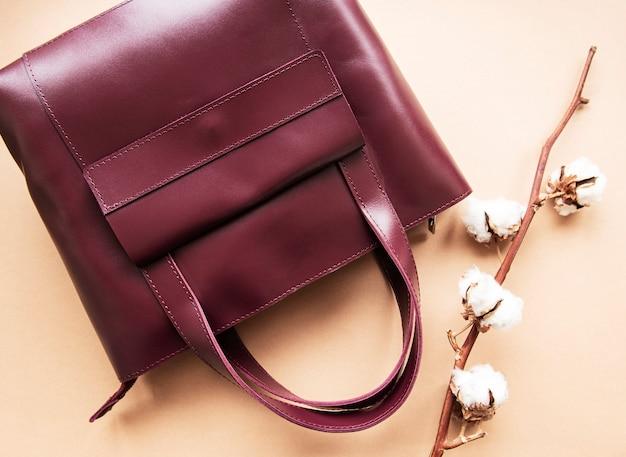 Красная кожаная сумка с хлопковыми цветами на коричневой поверхности