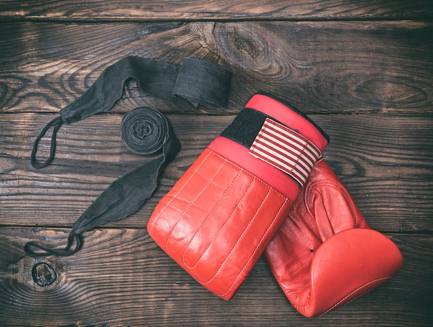 Red leather boxing gloves and black bandage
