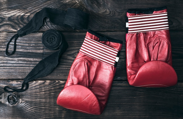 Red leather boxing gloves and a black elastic bandage