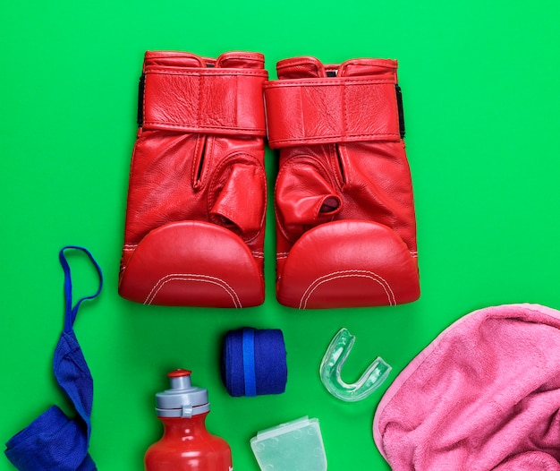Red leather boxing gloves, a plastic water bottle and a pink towel and blue textile bandage