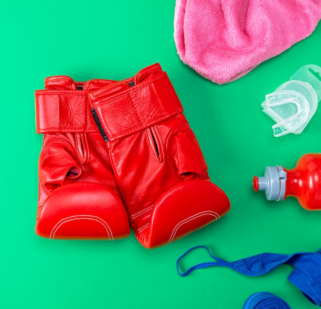 Red leather boxing gloves, a plastic water bottle and a pink towel