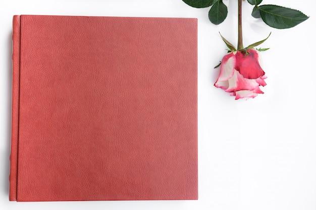 赤い革覆われた結婚式のアルバムとローズは、白い背景にあります。