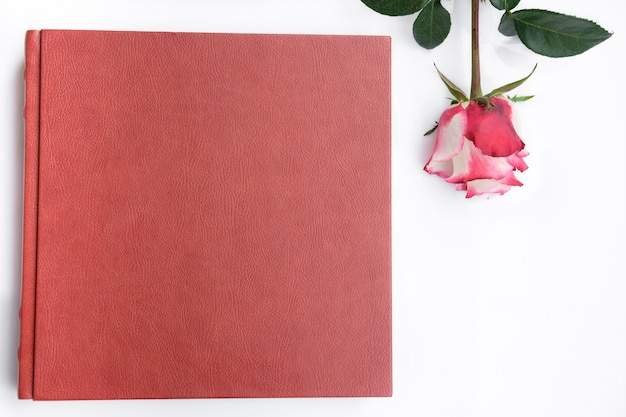 Red leather covered wedding album and rose lies on white background.