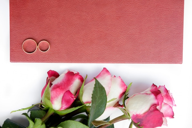Red leather covered wedding book or album with two wedding rings and three roses lies on white background.