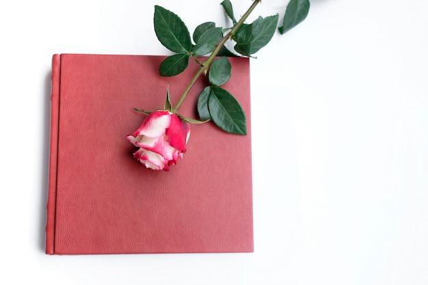 赤い革覆われた結婚式の本または結婚式のアルバムは白い背景にあり、1つのバラは結婚式の本にあります。