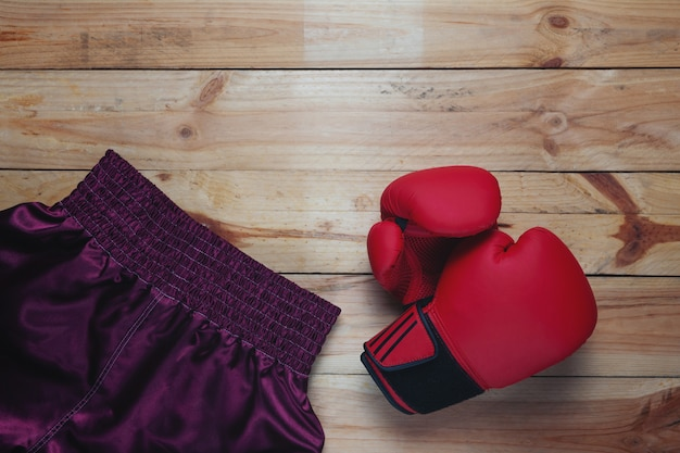 Red leather mitt glove and boxing pants on wooden table