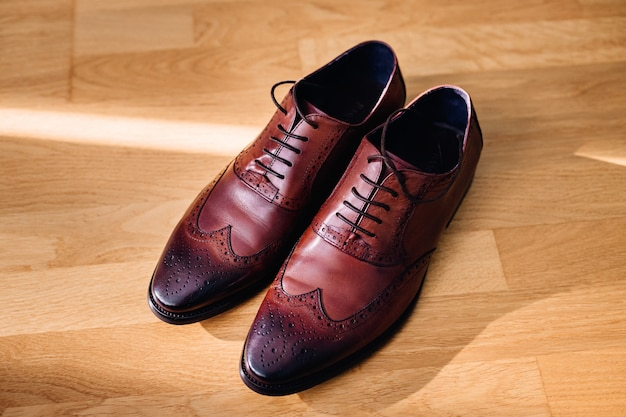 Red leather shoes stand on the light wooden floor