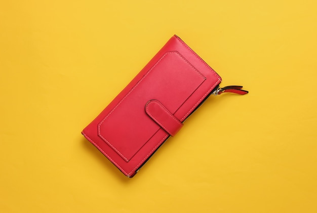 Красный кожаный кошелек на желтом фоне