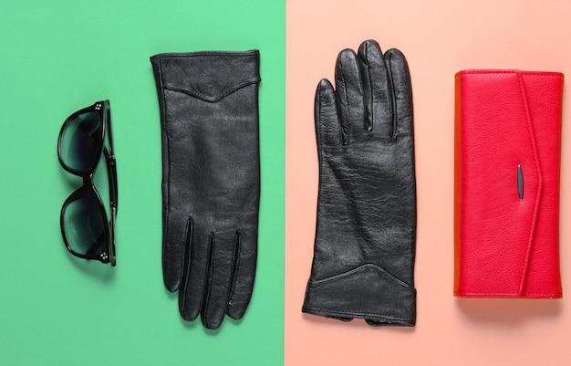 Красный кожаный бумажник, солнцезащитные очки, макро перчатки на цветном фоне. вид сверху