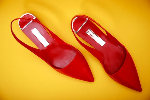 Red leather woman shoes isolated on yellow