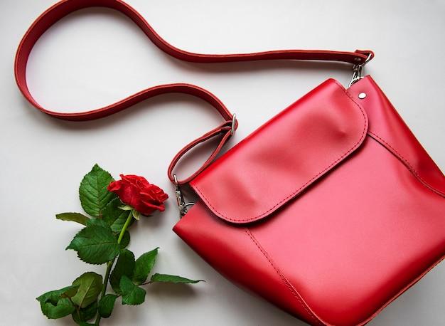 Красная кожаная женская сумка и роза на сером