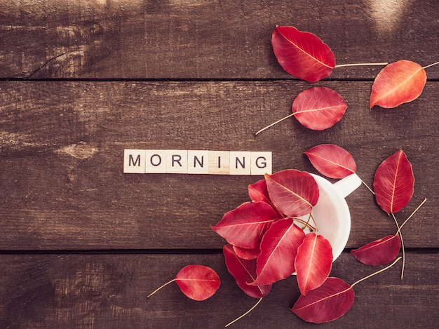 Red leaves, word morning and wooden surface