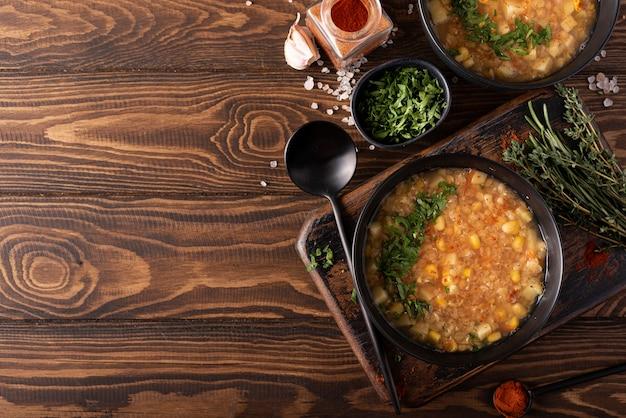 木製のテーブルの上の黒いボウルにハーブとパプリカと赤レンズ豆とコーンスープ