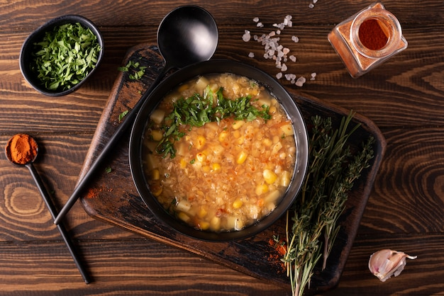 Red lentil and corn soup with herbs and paprika in a black bowl on a wooden table