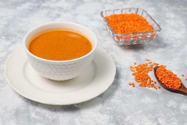 Крем суп из красной чечевицы на свет в белой миске, вид сверху