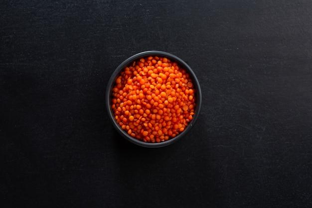 어두운 배경에 그릇에 빨간 렌즈 콩입니다. 목업. 평면도