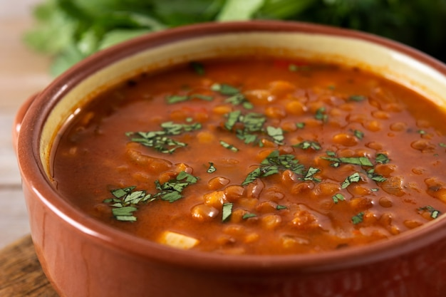 Суп из красной чечевицы в миске на деревенском деревянном столе