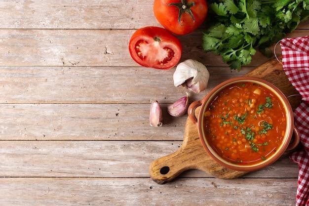 木製のテーブルのボウルに赤レンズ豆のスープ