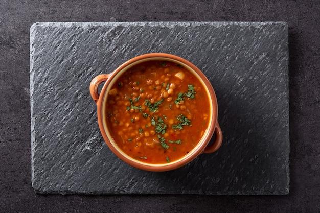 黒のスレートの背景に赤レンズ豆のスープ