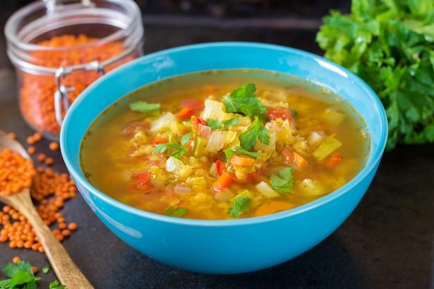 暗い背景に赤レンズ豆のスープ。健康的な食事のコンセプトです。