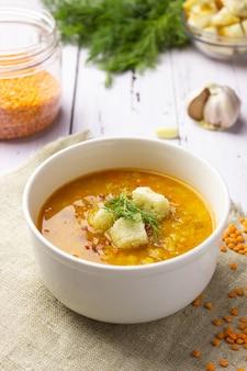 明るい背景に食材を使った赤レンズ豆のスープ。伝統的なトルコまたはアラビアのスパイシーなレンズ豆と野菜のスープ、健康的なビーガンフード。側面図、垂直方向。