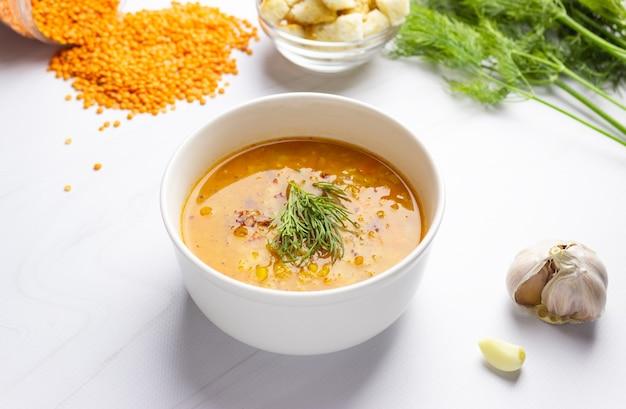 明るい背景に食材を使った赤レンズ豆のスープ。伝統的なトルコまたはアラビアのスパイシーなレンズ豆と野菜のスープ、健康的なビーガンフード。側面図