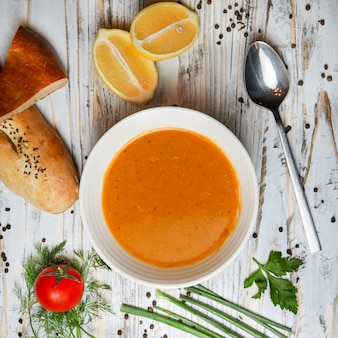 Red lentil soup with lemon, tomato, bread, herbs, spice, spoon in a bowl