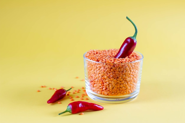 Red lentils in a glass jar with red chili peppers on a yellow background. healthy food concept, color trend, food wallpaper, copy space