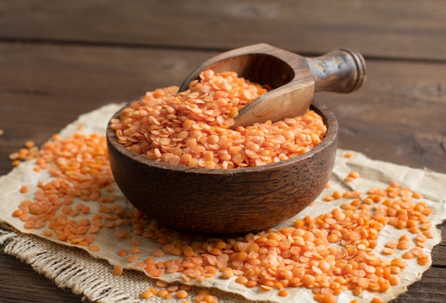 Красная чечевица в миске с ложкой на деревянном столе