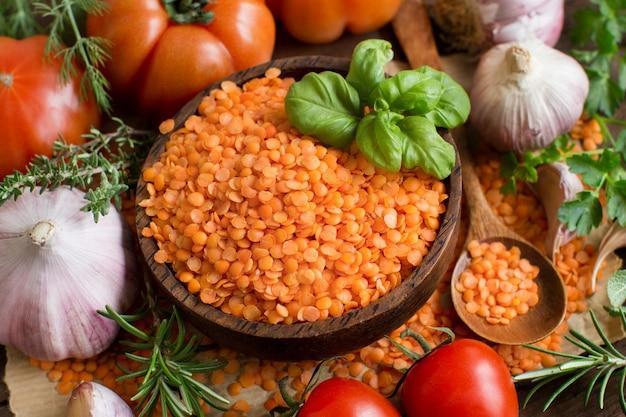 Красная чечевица в миске с помидорами, чесноком и зеленью