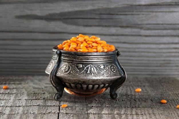 Red lentils in vintage silver jar on old wooden background.