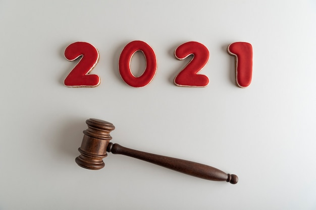 Red lettering 2021 and judges gavel or hammer on white background. court case.