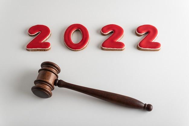 2022年の赤いレタリングと白い背景にガベルまたはハンマーを判断します。新年の訴訟