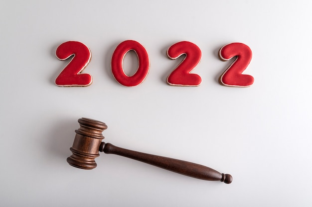 Red lettering 2022 and judges gavel or hammer on white background. court case in new year
