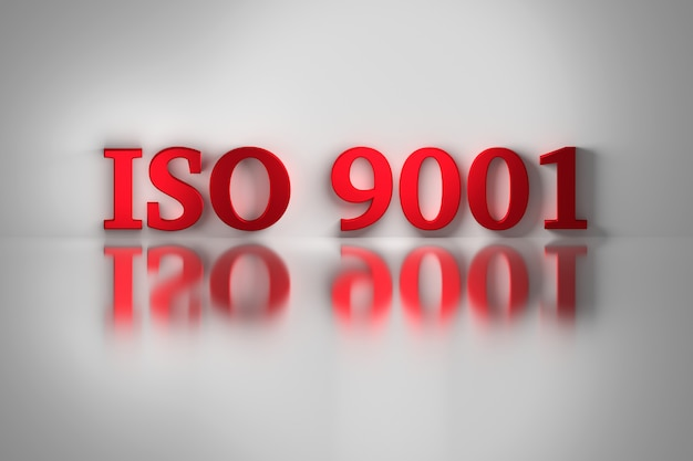 Red letters of iso 9001 quality standard for a quality management system reflected on the white surface.