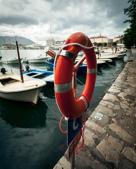 雨の日に海の港にぶら下がっている赤い救命浮環