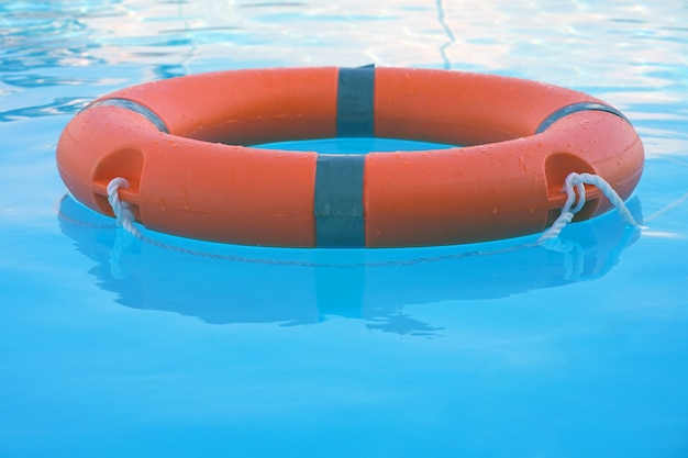 Red lifebuoy pool ring float on blue water. life ring floating on top of sunny blue water. life ring in swimming pool