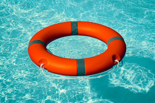 Red lifebuoy pool ring float on blue water.