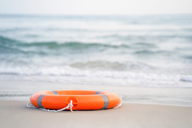 Red lifebuoy pool ring float. life ring on the sea sand.