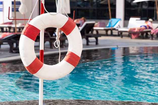 スイミングプールの近くの赤い救命浮輪リング