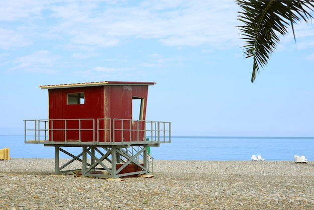 空のビーチに赤いライフガード小屋
