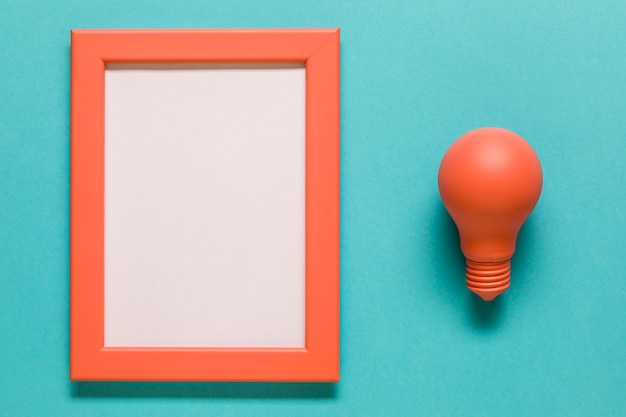 Red light bulb and empty frame on blue background