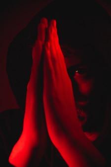 Красный свет над человеком с руками в молитве