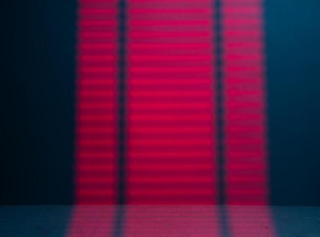 Красный свет проходит через жалюзи и падает на стену