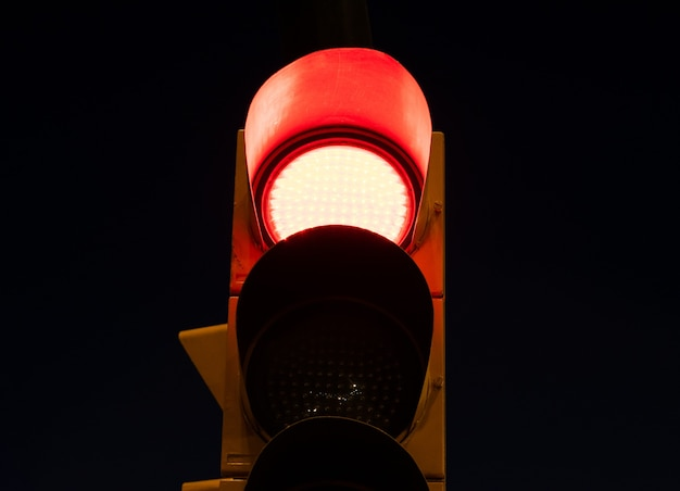 Red light on a traffic light at the street at night