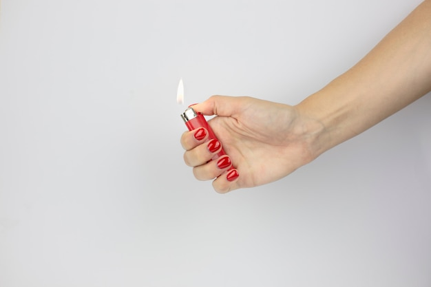 Red lighter with fire in woman's hand with red nails isolated on white wall
